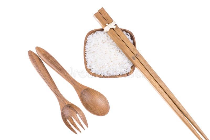 Fourchette, cuillère et baguettes en bois naturelles avec du riz dans la cuvette photos stock