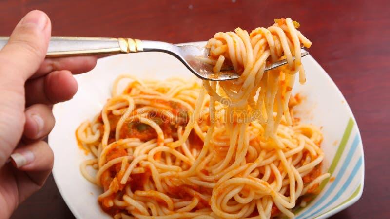Fourchette de prise de main avec des spaghetti photos stock
