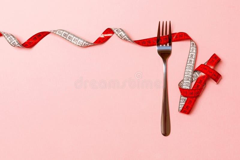 Fourchette entourée avec le ruban métrique courbé sur le fond rose avec l'espace de copie Vue supérieure de concept approprié de  photos libres de droits