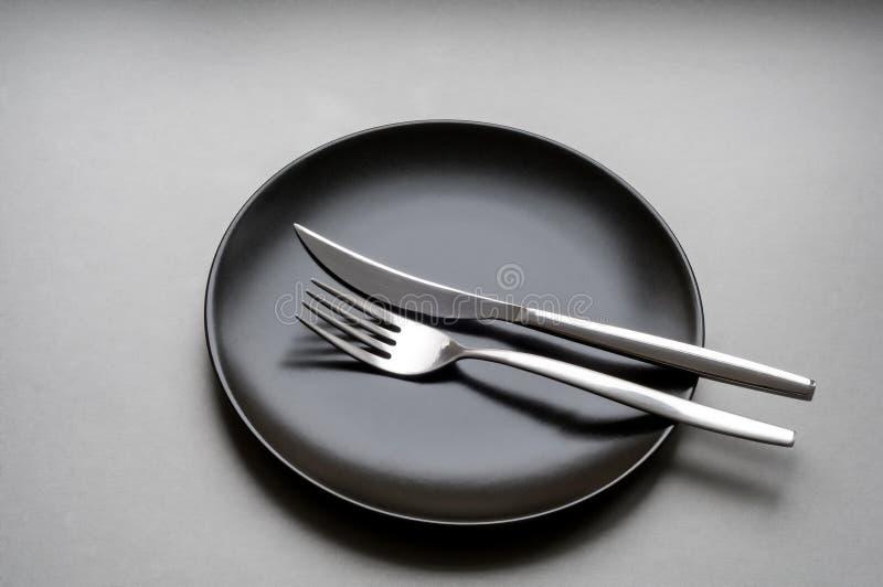 Fourchette et couteau d'un plat noir photographie stock libre de droits