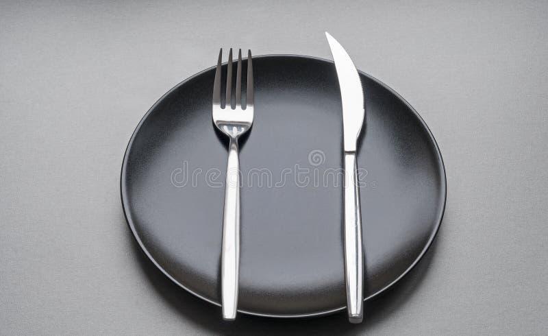 Fourchette et couteau d'un plat noir photos libres de droits