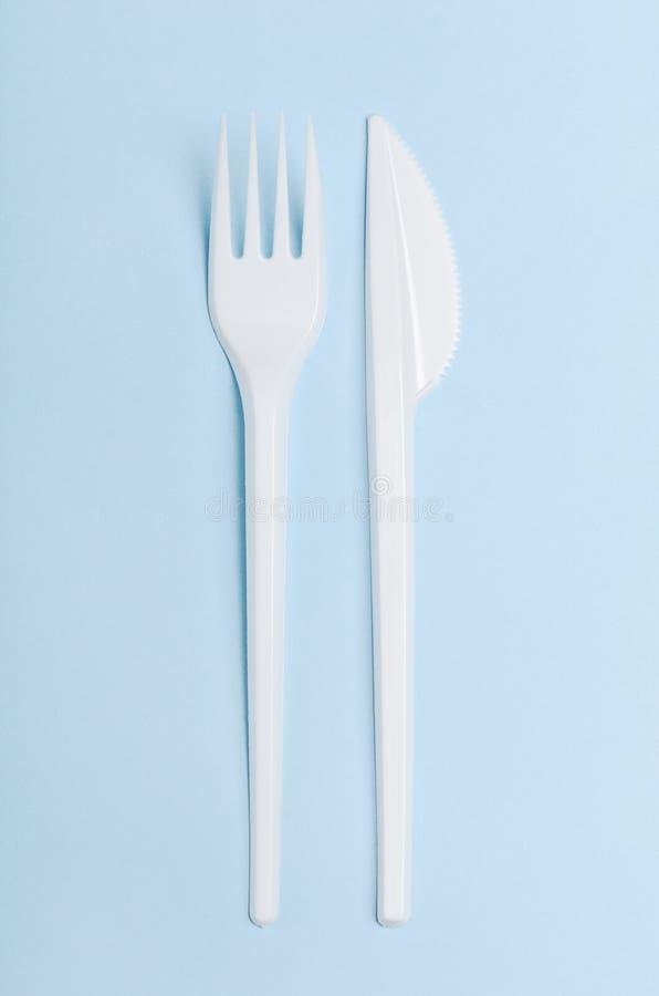 Fourchette et couteau jetables blancs en plastique sur un fond bleu Plats en plastique de concept, aliments de préparation rapide photographie stock libre de droits