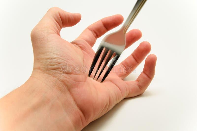 Fourchette poignardant une paume de main sur le fond blanc image stock
