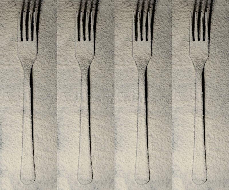 Fourchettes de couverts sur une surface plane arrosée avec de la farine blanche images stock