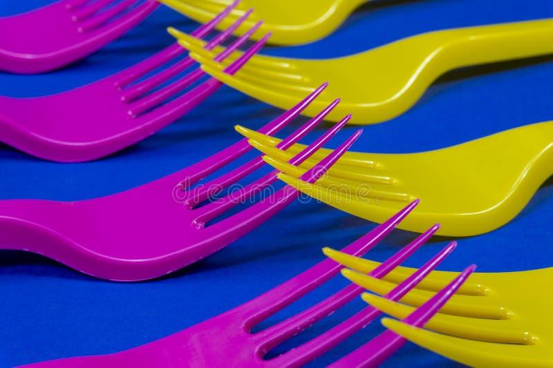 Fourchettes en plastique pourpres et jaunes colorées sur le bleu images stock