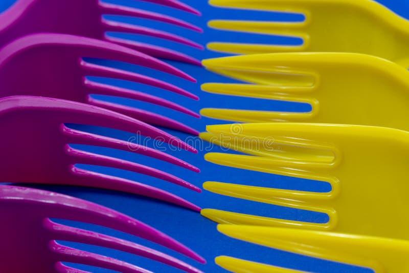 Fourchettes en plastique pourpres et jaunes colorées sur le bleu photographie stock