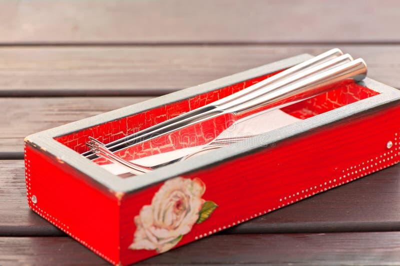 Fourchettes et couteaux métalliques brillants dans la boîte en bois rouge images libres de droits