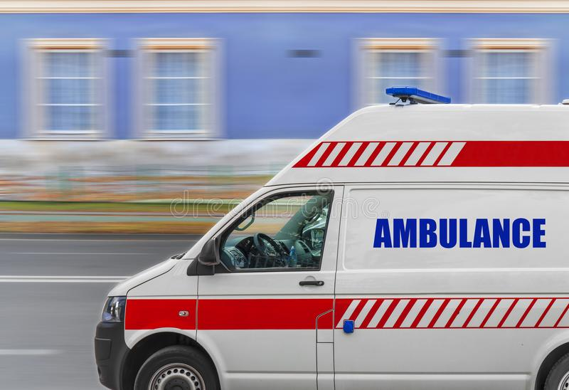 Fourgon de service d'ambulance conduisant rapidement sur la rue photo stock