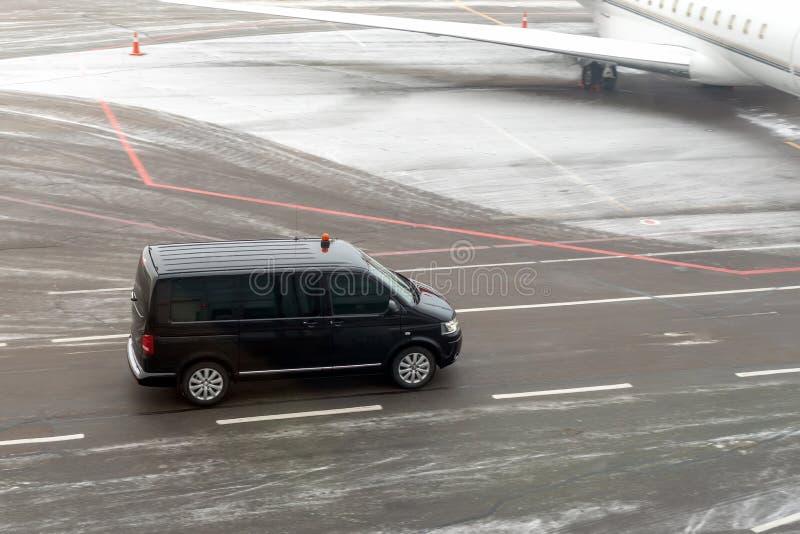 Fourgon noir de service de VIP fonctionnant sur la piste de roulement d'aéroport avec le jet privé brouillé sur le fond Service d photographie stock