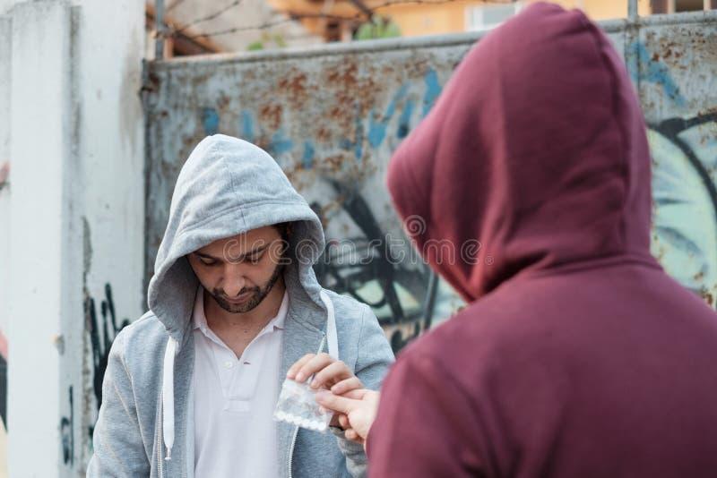Fournisseur et toxicomane échangeant l'argent et la drogue images stock