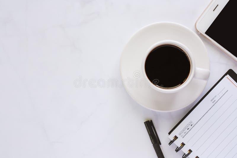 Fournitures de bureau avec le carnet de notes à spirale, le stylo, la tasse de café et le sma image stock