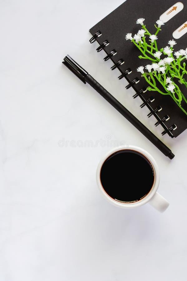 Fournitures de bureau avec le carnet de notes à spirale, stylo, tasse de café noir a photographie stock