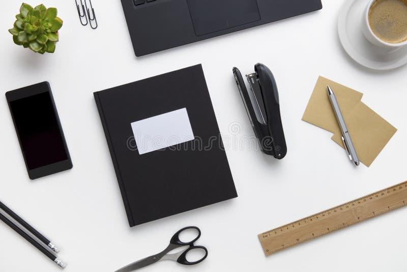 Fournitures de bureau et dispositifs disposés sur le bureau blanc image libre de droits