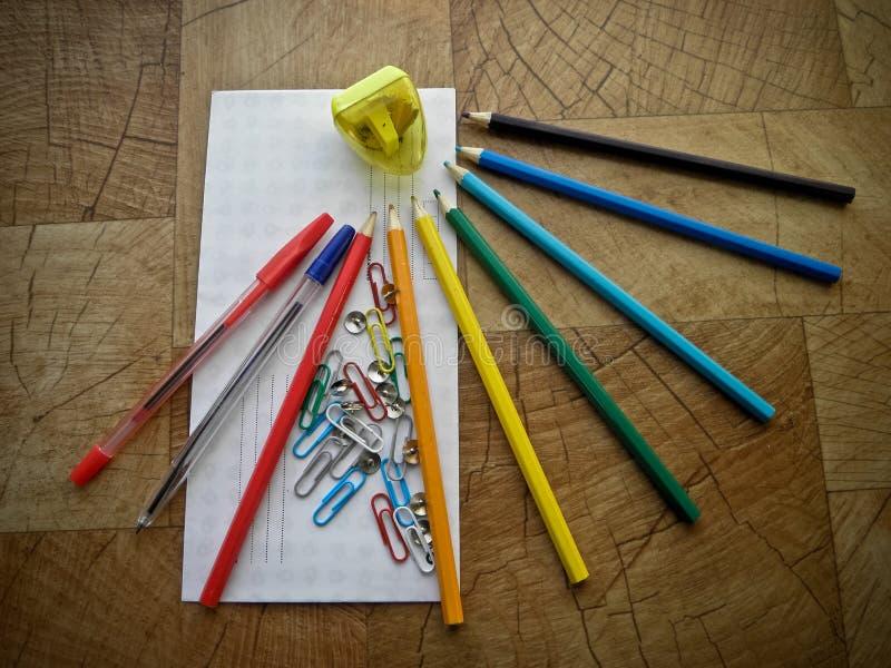 Fournitures de bureau multicolores sur une table en bois photos stock