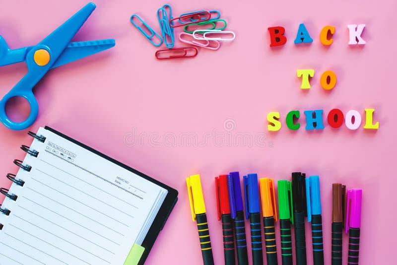 Fournitures scolaires avec le texte en bois DE NOUVEAU À L'ÉCOLE sur le backgrou rose photo libre de droits