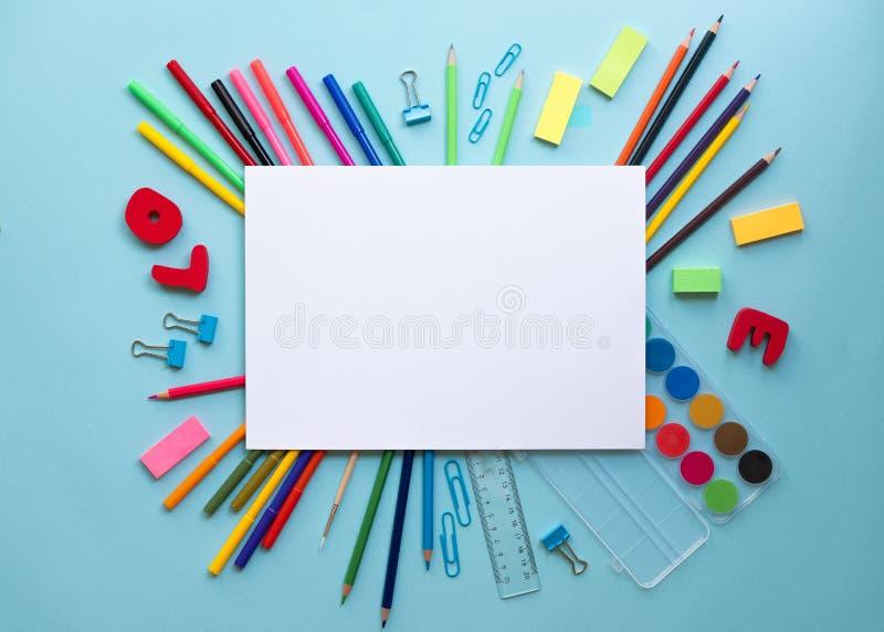 Fournitures scolaires colorées au-dessus d'un papier sur le fond bleu avec l'endroit pour votre texte images libres de droits