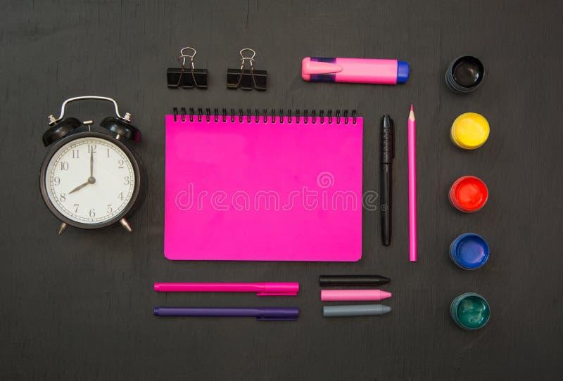 Fournitures scolaires colorées, cahier pourpre et réveil sur le tableau noir Vue supérieure, configuration plate, l'espace de cop image libre de droits