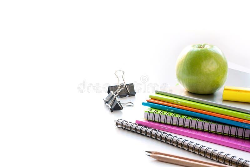 Fournitures scolaires colorées, livre, pomme sur le blanc Fin vers le haut De nouveau à l'école photographie stock libre de droits