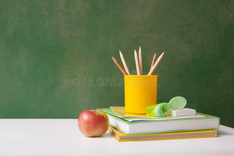 Fournitures scolaires dessus de nouveau au panneau de craie d'école photographie stock