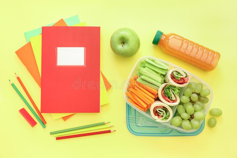 Fournitures scolaires et gamelle avec les petits pains savoureux, concombres, carottes, raisins, pomme, bouteille de jus sur jaun photographie stock