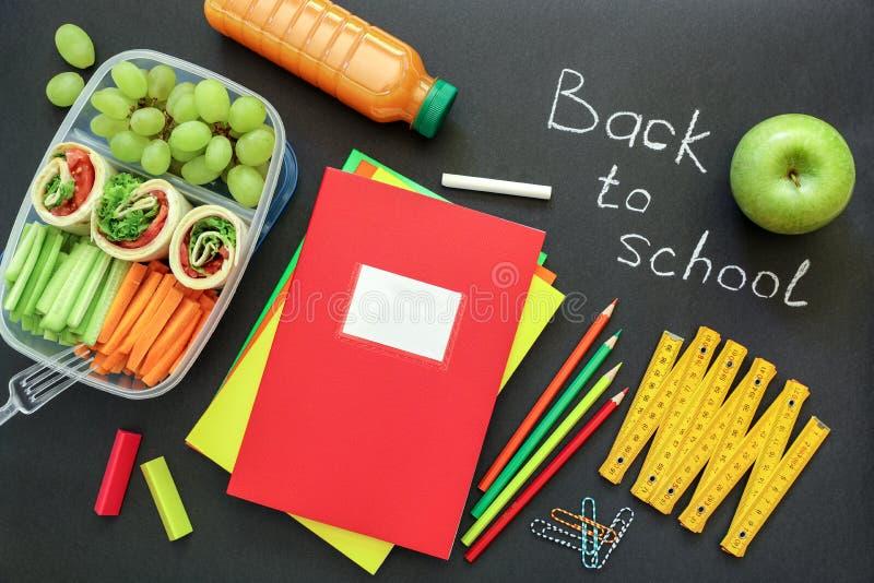 Fournitures scolaires et gamelle avec les petits pains savoureux, concombres, carottes, raisins, pomme, bouteille de jus sur le f images stock