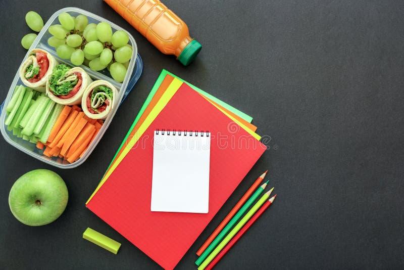 Fournitures scolaires et gamelle avec les petits pains savoureux, concombres, carottes, raisins, pomme, bouteille de jus sur le f photos libres de droits