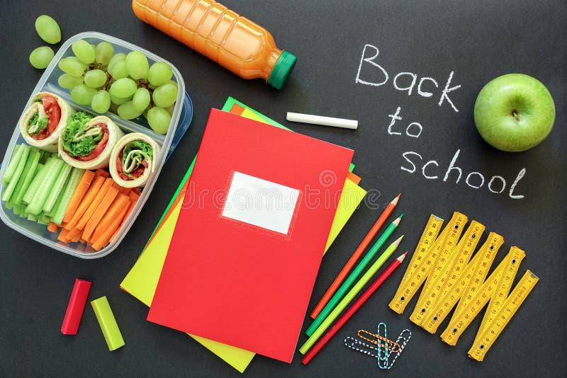 Fournitures scolaires et gamelle avec les petits pains savoureux, concombres, carottes, raisins, pomme, bouteille de jus sur le f images libres de droits