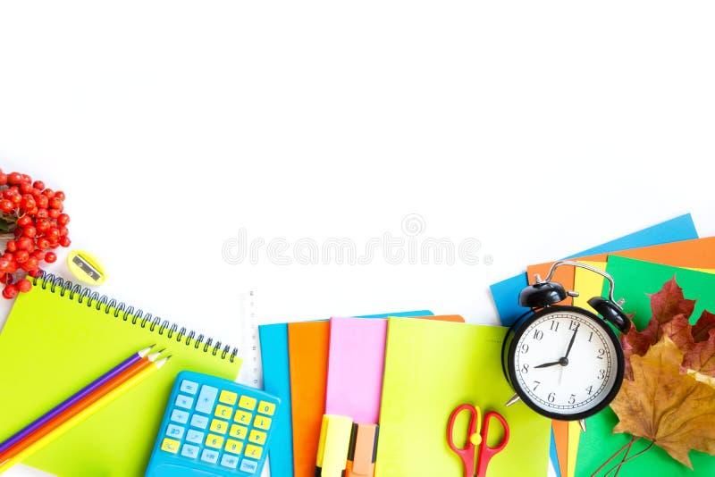 Fournitures scolaires, livre, et réveil colorés sur le blanc Vue supérieure, configuration plate Copiez l'espace image stock