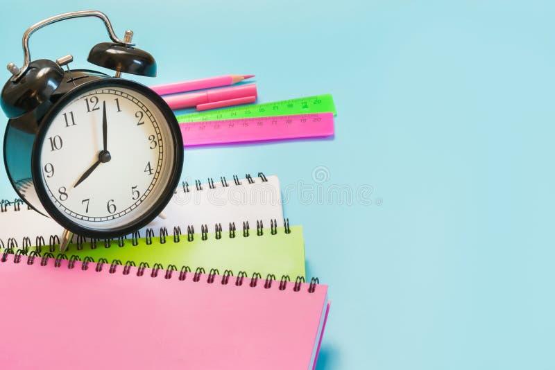 Fournitures scolaires, livre et réveil de fille colorés sur le bleu ivre Fin vers le haut De nouveau à l'école images stock