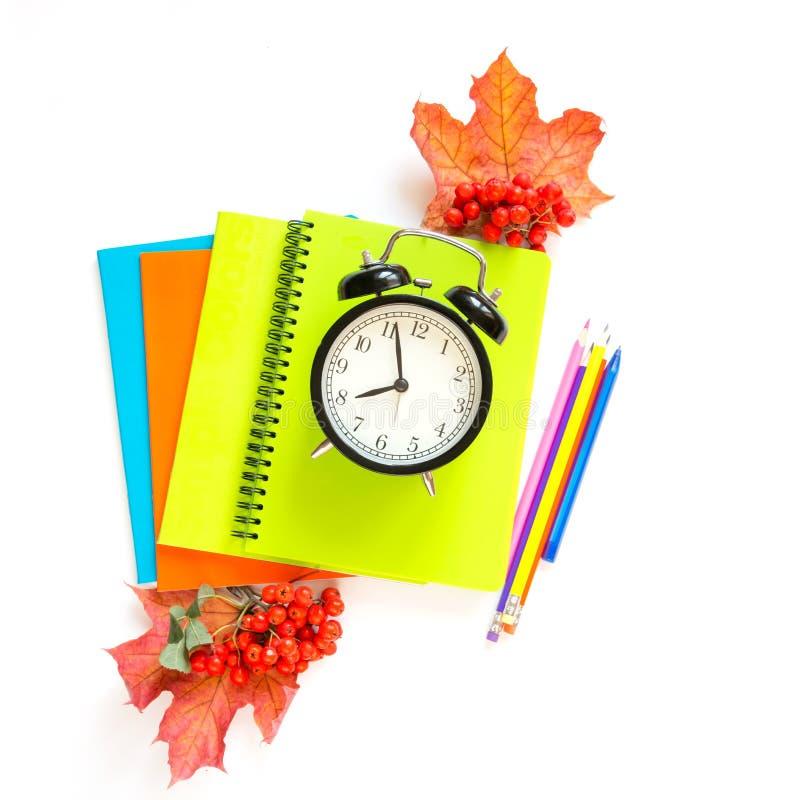 Fournitures scolaires, livres, réveil et crayon colorés sur le blanc Vue supérieure, configuration plate Image carrée photo libre de droits