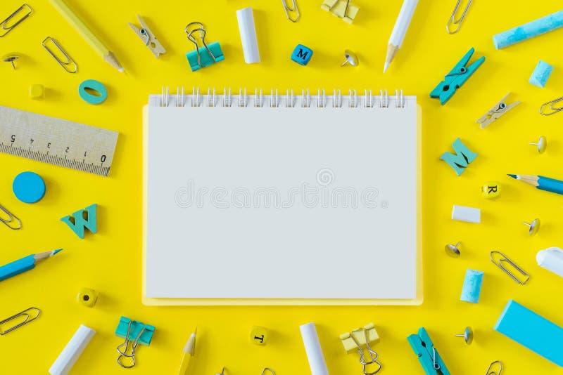 Fournitures scolaires multicolores sur le fond jaune avec l'espace de copie image stock