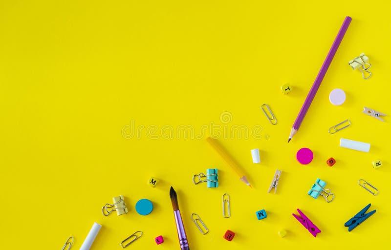 Fournitures scolaires multicolores sur le fond jaune avec l'espace de copie photographie stock libre de droits