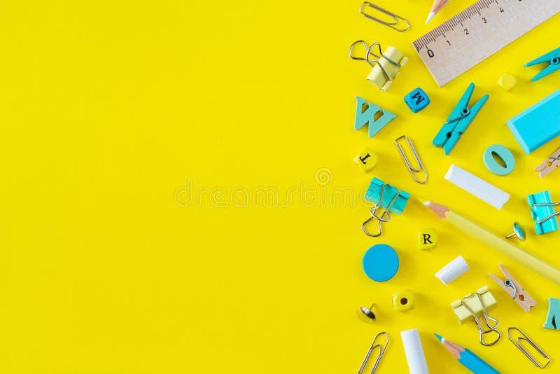 Fournitures scolaires multicolores sur le fond jaune avec l'espace de copie photo libre de droits