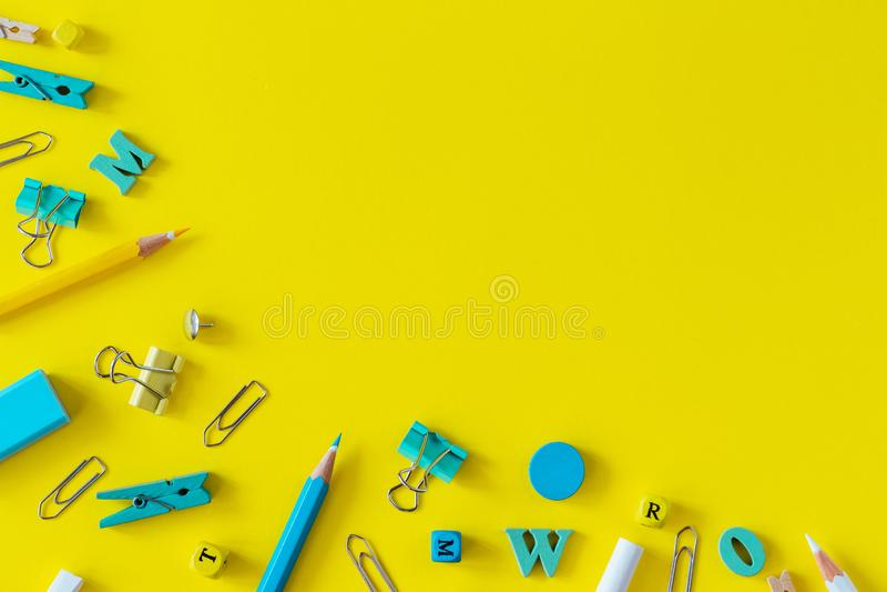 Fournitures scolaires multicolores sur le fond jaune avec l'espace de copie photos stock
