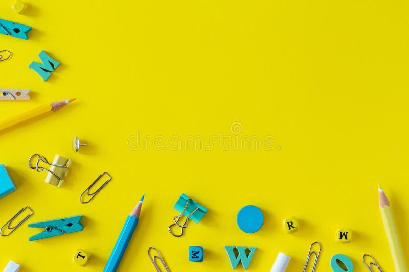 Fournitures scolaires multicolores sur le fond jaune avec l'espace de copie images libres de droits
