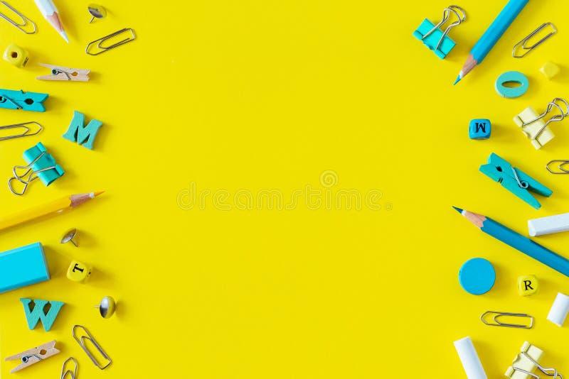Fournitures scolaires multicolores sur le fond jaune avec l'espace de copie photographie stock
