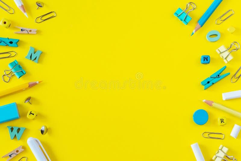 Fournitures scolaires multicolores sur le fond jaune avec l'espace de copie image libre de droits