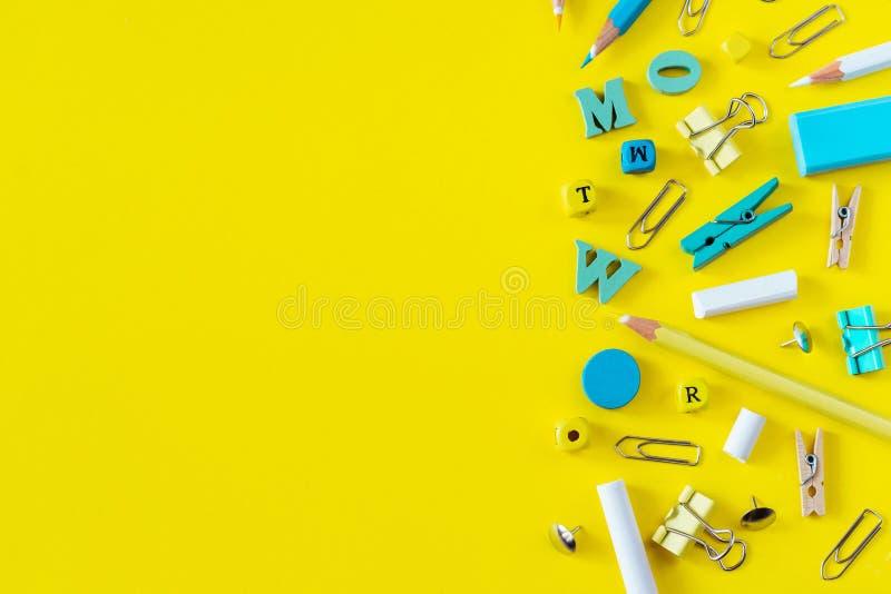 Fournitures scolaires multicolores sur le fond jaune avec l'espace de copie images stock