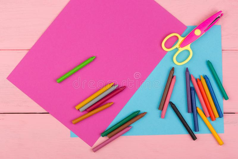 fournitures scolaires : papier de marqueurs, de crayons, rose et bleu, ciseaux sur la table en bois rose image libre de droits
