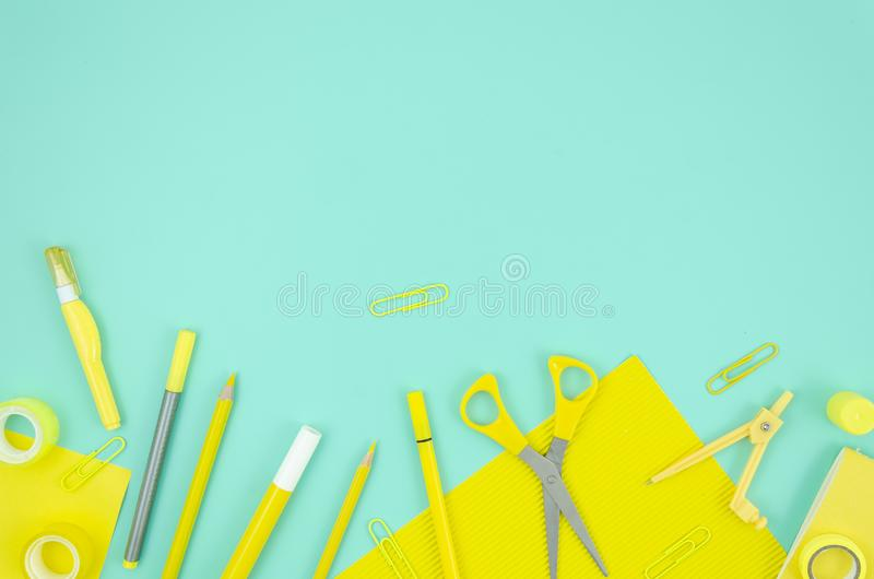 Fournitures scolaires stationnaires jaunes étendues plates de cadre sur le fond bleu Copiez l'espace pour le texte De nouveau au  photographie stock libre de droits