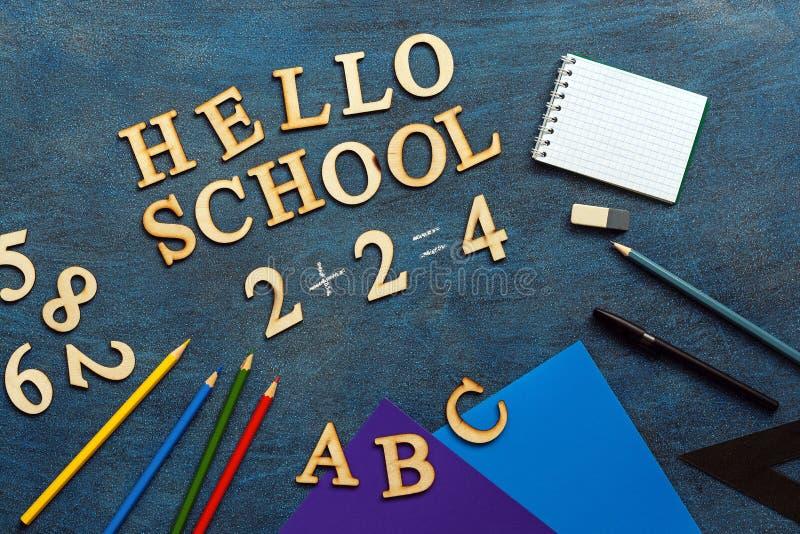 Fournitures scolaires sur un fond rustique bleu-foncé Bonjour, école, texte des lettres en bois Configuration plate, vue sup?rieu image stock