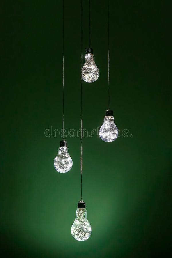 A foursome of amazing uncommon electric lamps in front of green background royalty free stock photo