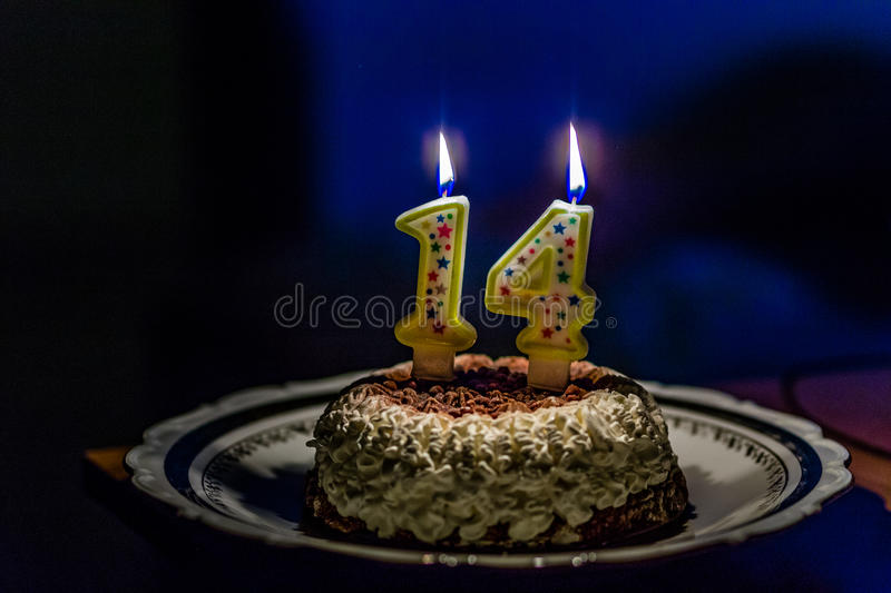 Fourteen birthday cake with number candles. Cream and chocolate cake with lit number one and number four candles to celebrate fourteen years birthday in dark stock images