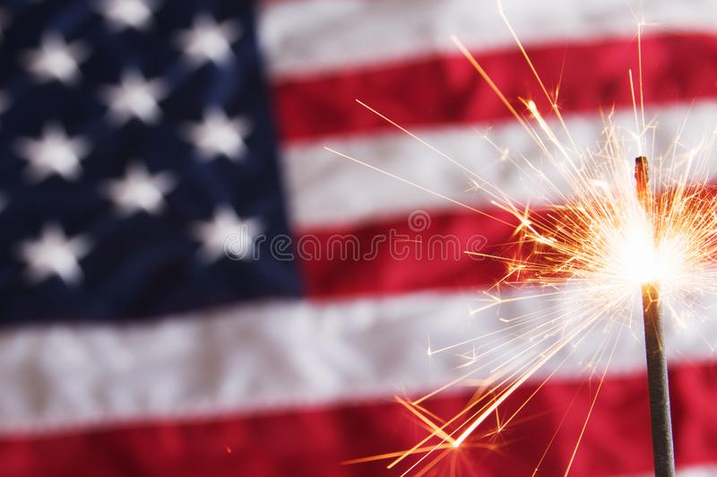 Fourth of July Sparkler. A fourth of july sparkler on a usa flag background