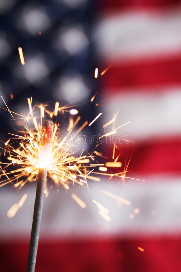 Fourth of July Sparkler. A fourth of july sparkler on a usa flag background stock image