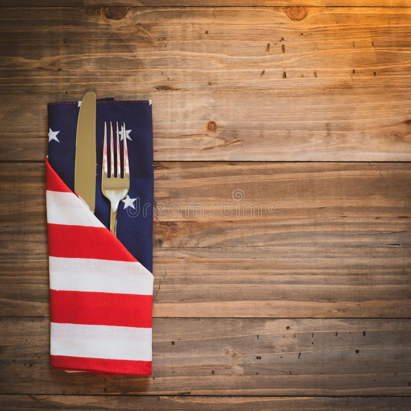 Fourth of July Table Place Setting with a fork, knife and flag napkin in warm light on rustic wood board background with room or s royalty free stock photography