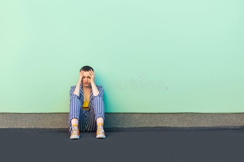 Fout, droefheid of depressie Portret van droevige alleen korte haar jonge vrouw in toevallige gestreepte kostuumzitting op vloer, royalty-vrije stock foto's