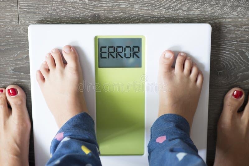 Foutenmelding op de vertoning van de badkamersschaal, zwaarlijvig kind die onder parent'ssupervisie wegen stock afbeeldingen