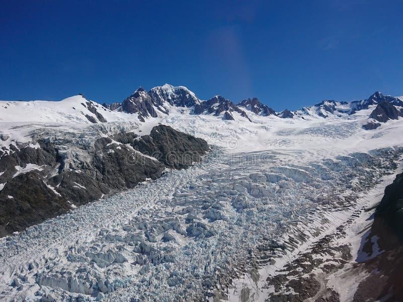 Fox冰川冬天雪山有山和明白蓝天背景,新西兰 免版税库存照片