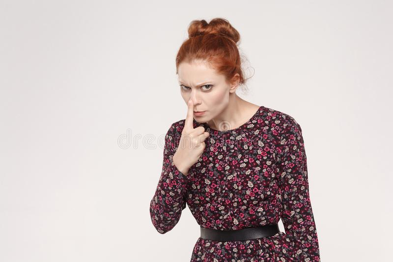 Foxy lady have a badmood, touching her nose and looking at camera with anger. Isolated on gray background stock photo